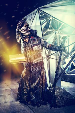 ethnic dress: Ritratto di uno sciamano di sesso maschile in abito etnico su un esterno futuristico. Concetto di fantasia, magia.