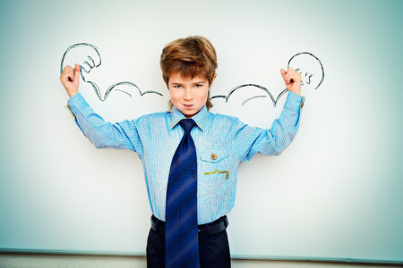 Smart boy stands by the whiteboard in a classroom expressing the power of knowledge. Educational concept. Copy space. photo