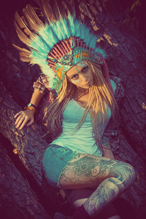 chieftain: Attractive modern girl in style of the American Indians. Western style. Jeans fashion. Tattoo.