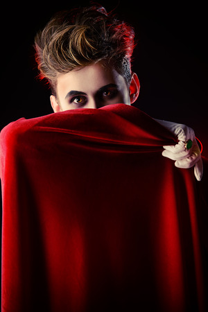 bloodthirsty: Handsome vampire hiding his face behind his cloak. Halloween. Dracula costume. Stock Photo