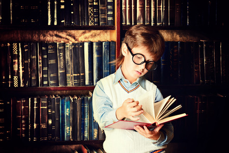 old and young: Smart boy stands in the library by the bookshelves with many old books. Educational concept. Science.