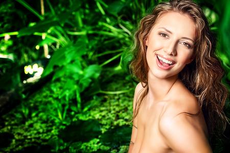 wet bikini: Beautiful laughing young woman in bikini in the rainforest. Vacation. Tropics.