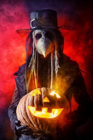 contagion: Frightening plague doctor stands with a pumpkin. Medieval Europe. Halloween.