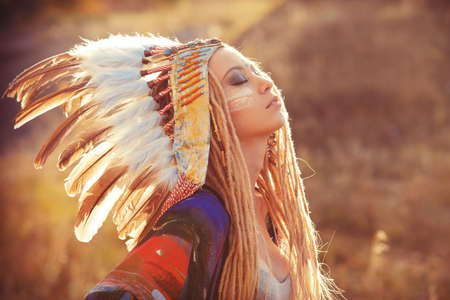 Close-up portrait of a beautiful girl wearing native american indian chief headdress. Western style. Jeans fashion.