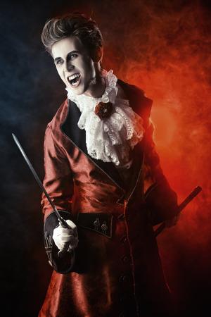 Handsome bloodthirsty vampire. Halloween. Dracula costume. photo