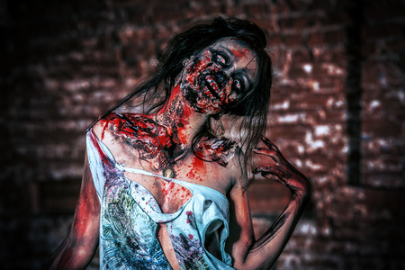 Horrible bloody zombie girl standing outdoor by the brick wall. Halloween. photo