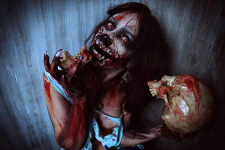 frightening: Frightening bloody zombie girl with a skull. Halloween.