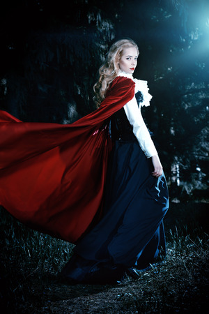 Beautiful blonde woman in  old-fashioned dress and red cloak in a fairy forest.