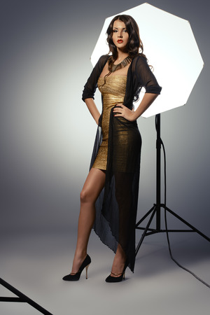 Fashion shot of a gorgeous young woman in golden dress posing at studio. photo
