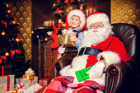 cor: Santa Claus and laughing cute boy sitting in Christmas room with gifts. Christmas home décor.