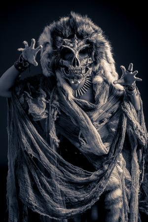 Frightening female wearing mask of skull. Fantasy. Halloween. Witchcraft, voodoo dances. photo