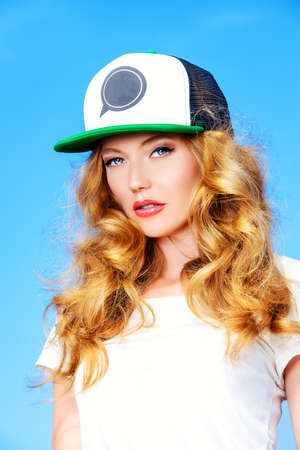 Portrait of a charming girl in teens hat against the blue sky. photo