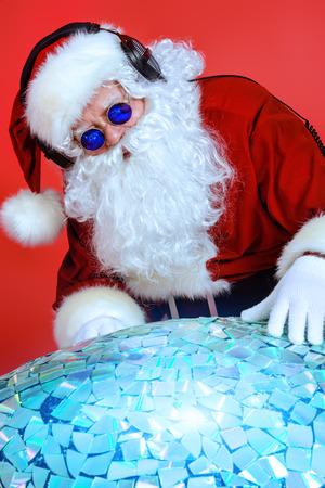 Santa Claus DJ near brilliant sparkling disco ball. Christmas celebration. photo