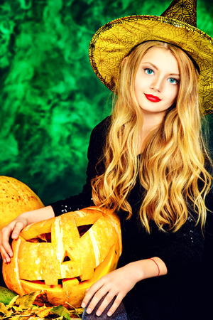 Pretty blonde girl teenager in a costume of witch posing with pumpkins over dark smoky background. Halloween. photo
