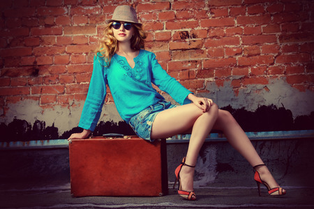 femme valise: Portrait d'une belle jeune femme assise sur sa vieille valise près de la mur de briques. photo de mode.