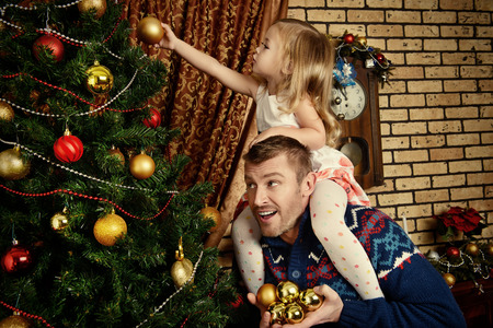 young tree: Happy father and his little daughter decorating the Christmas tree at home. Stock Photo