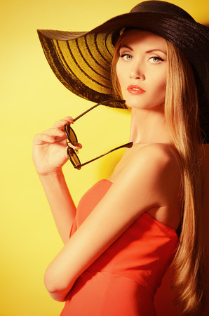 Portrait of a stunning fashionable lady over bright yellow background. Beauty, fashion concept. Optics. photo
