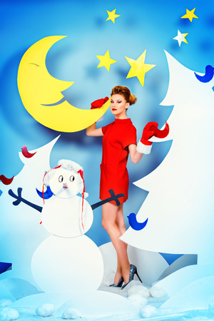 Attractive young woman in festive red dress posing in Christmas decorations. Fashion shot. photo
