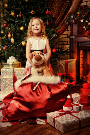 Happy girl holds a gift at home by the Christmas tree. photo