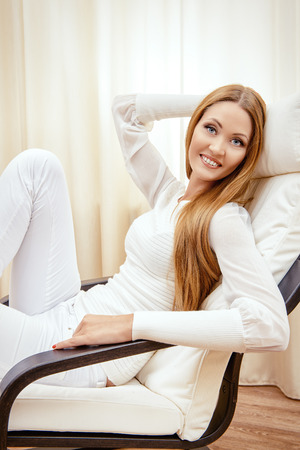 Happy young woman resting at home in a comfortable chair. photo