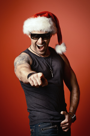 tempter: Portrait of a cheerful handsome brutal man in Christmas hat. Over red background. Stock Photo