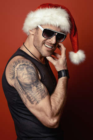tempter: Portrait of a handsome brutal man in Christmas hat. Over red background.