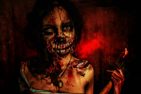 frightening: Scary bloody zombie girl with an ax. Halloween.