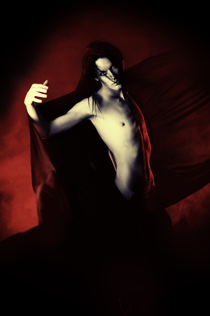 Handsome gothic man over dark background. photo