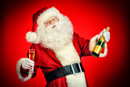 Santa Claus with a glass of champagne wishes all a Merry Christmas. Over festive red background. photo