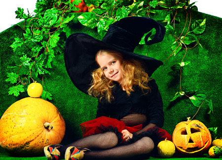 Cute little girl in a witch costume posing with pumpkins. Halloween. photo