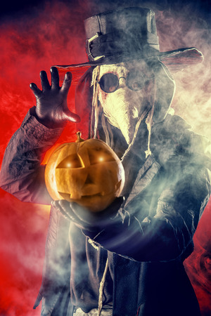 Frightening plague doctor stands with a pumpkin. Medieval Europe. Halloween. photo