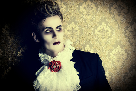 beautiful vampire: Portrait of a handsome male vampire over vintage background. Halloween. Dracula costume.