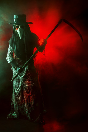 plague: Portrait of a terrible plague doctor with a scythe. Medieval Europe. Halloween. Stock Photo