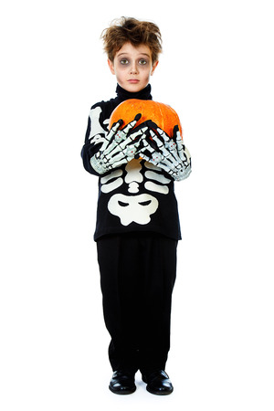 Funny boy in a costume of skeleton holds a pumpkin. Halloween party. Isolated over white.