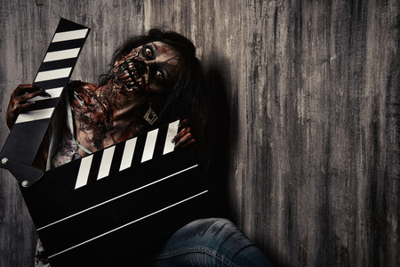 creepy: Filming a horror movie. Female zombie holding clapper board. Cinematography. Halloween.