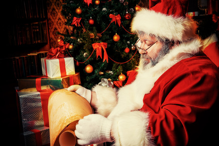 Santa Claus sitting in a room decorated for Christmas, and carefully read the list of good boys and girls. Christmastime. photo