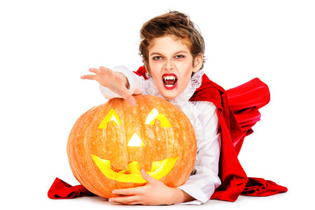 Cool teen boy in a costume of vampire posing with pumpkin with different emotions. Halloween. photo