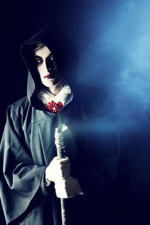 Gloomy, scary vampire in a black cloak hiding his face under a hood. Halloween. photo