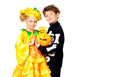 Cute boy and a girl wearing halloween costumes posing with pumpkin. Halloween. Isolated over white. photo