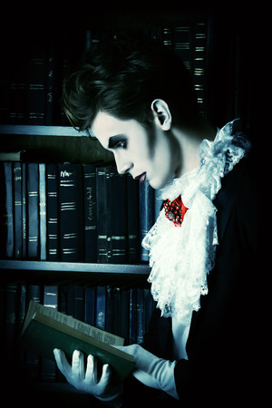 Handsome vampire nobleman studying ancient books in the library. Halloween. Dracula costume. photo
