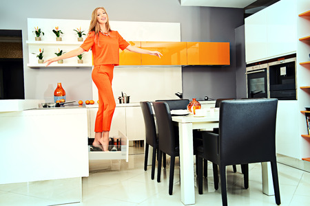 Cheerful young woman demonstrates the high quality of the kitchen furniture. Home interior. photo