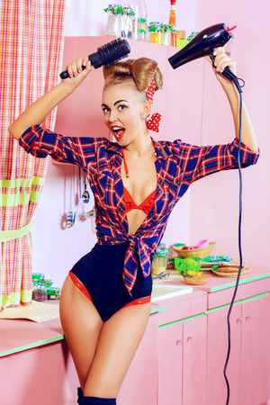 Beautiful pin-up girl doing a hair with a hair dryer and comb on her pink kitchen. Retro style. Fashion. photo