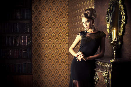 luxury room: Elegant young woman in black evening dress posing in vintage interior. Fashion shot.