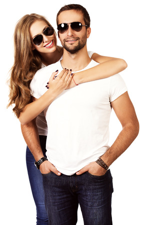 Happy young couple in love posing at studio. Isolated over white. photo