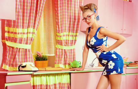 Pretty pin-up girl on a pink kitchen. Retro style. Fashion. photo