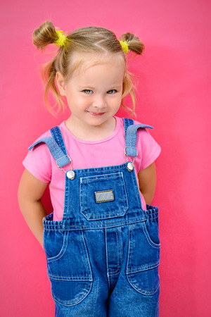 Portrait of a cute little girl over bright pink background. Happy childhood. photo
