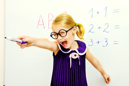 Little girl stands at the blackboard, points her finger and shouts.