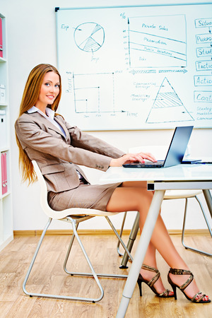 Young businesswoman working in the office with a laptop. photo