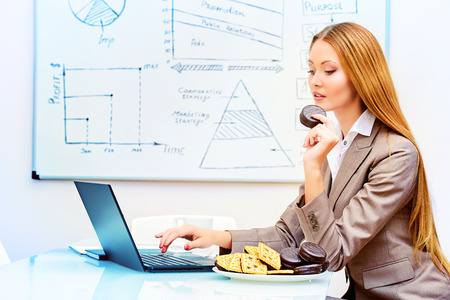 Beautiful businesswoman working in the office with a laptopn and eating cookies. photo