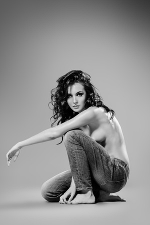 Sexual shirtless young woman alluring in jeans. Studio shot. Beauty, fashion. photo